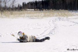 Frau mit Maske liegt im Schnee - Beitragsfoto: Die Sauna in Finnland und ihr Schutzgeist - Der Saunatonttu