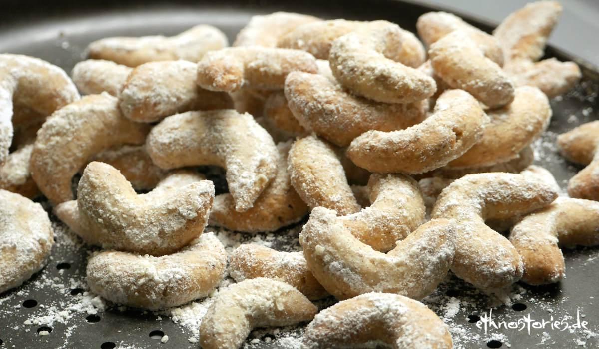 Viele mit Puderzucker bestreute Vanillekipferl liegen gehäuft auf einem Blech
